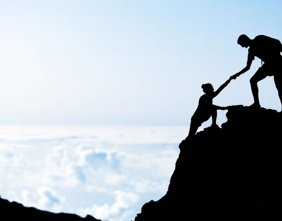 man helping woman up the mountain mentoring